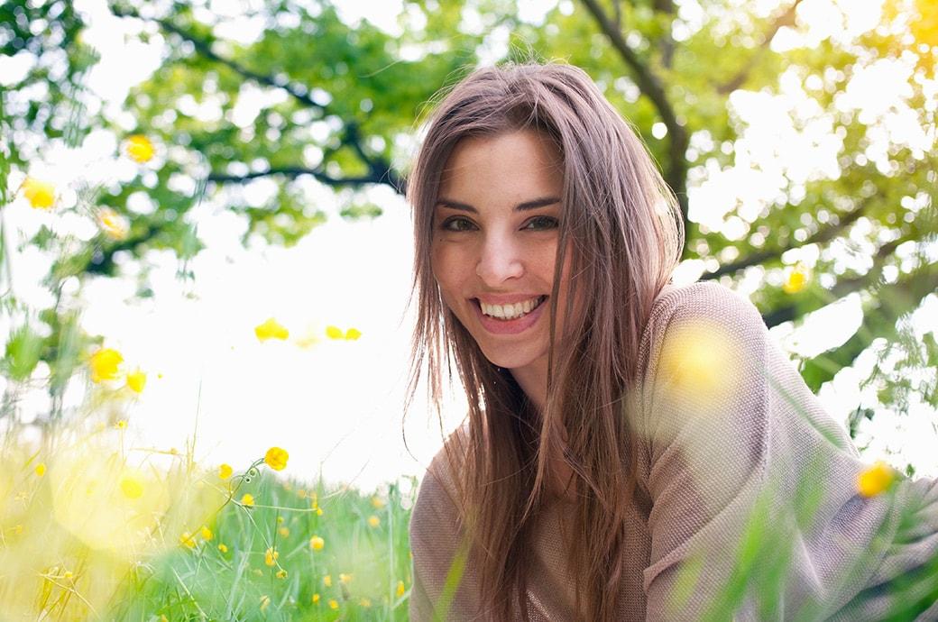 אישה בוגרת מחייכת כשהיא שוכבת על הדשא באור השמש.