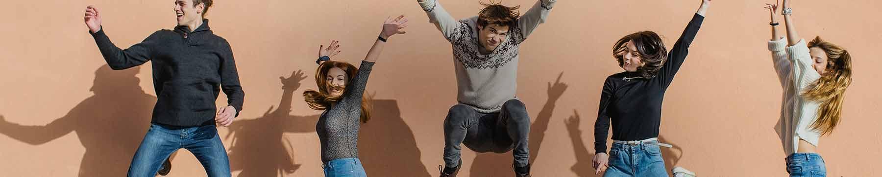 תמונה בתזמון מושלם של קבוצת חברים קופצת עם ידיים באוויר