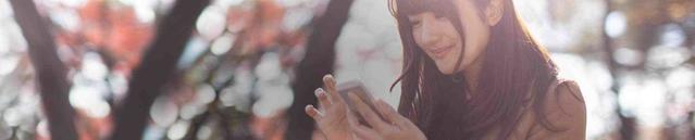 אישה צעירה בשטח פתוח מביטה בטלפון שלה