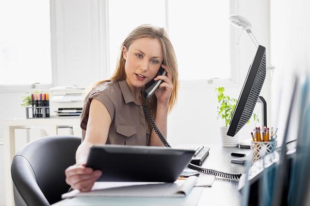אישה עובדת במשרד, מביטה במחשב לוח בזמן שיחת טלפון