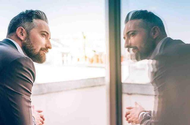 מונה של אדם בוגר המביט בהשתקפות של עצמו בחלון