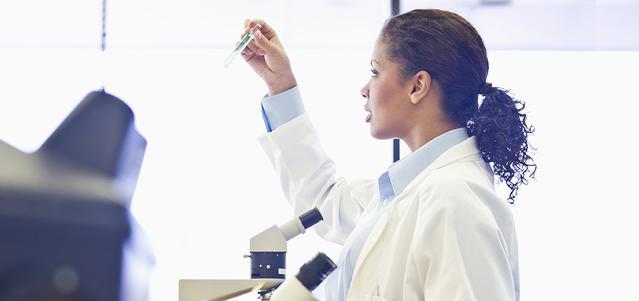 רופא בחלוק מעבדה מתבונן במבחנה