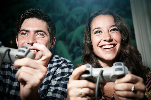 שני מבוגרים מחזיקים שלטים של משחקי וידאו