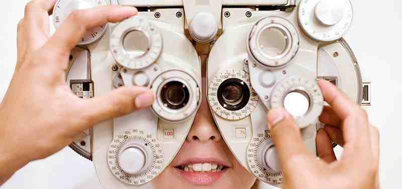 רופא במעבדה מול מיקרוסקופ בוחן מקרוב מבחנה