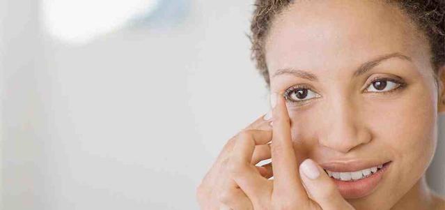אישה עם עדשת מגע על האצבע, רגע לפני שהיא מרכיבה אותה