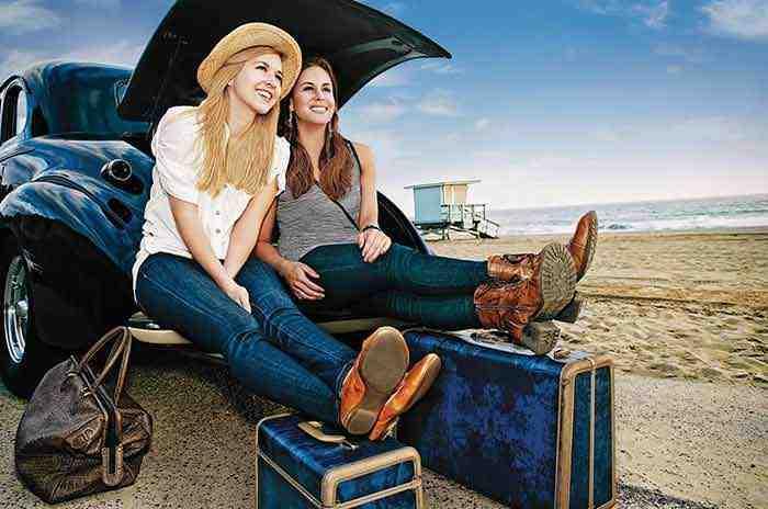 שתי נערות יושבות בתא מטען של רכב ליד החוף, עם מזוודות מוכנות ליציאה לחופשה.