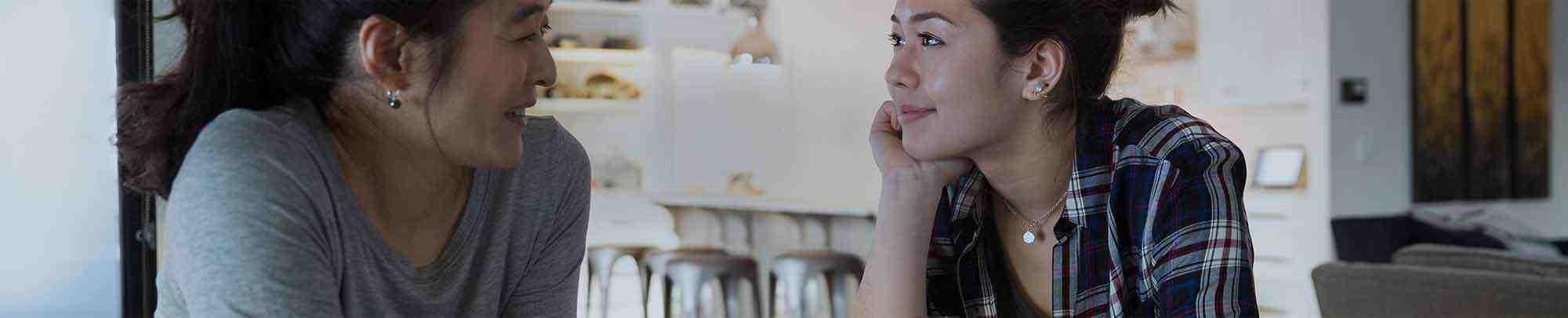 אישה צעירה משוחחת עם אימה במטבח