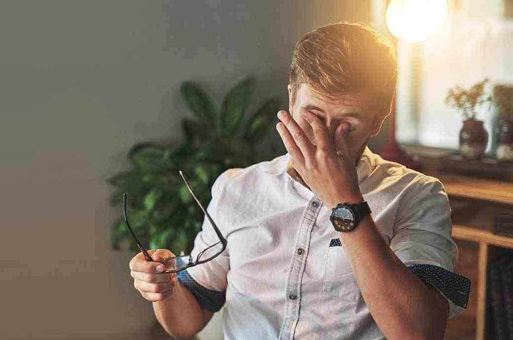 תמונה של איש המסיר את משקפיו כדי לשפשף את העיניים