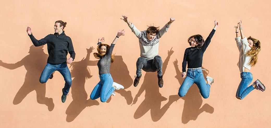 קבוצת חברים קופצת עם ידיים באוויר, צוחקת ומחייכת