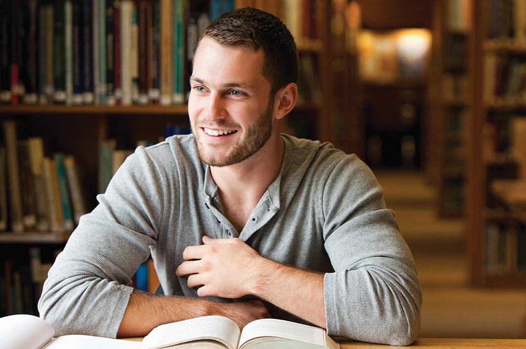 גבר בספרייה עם ספרים על השולחן.