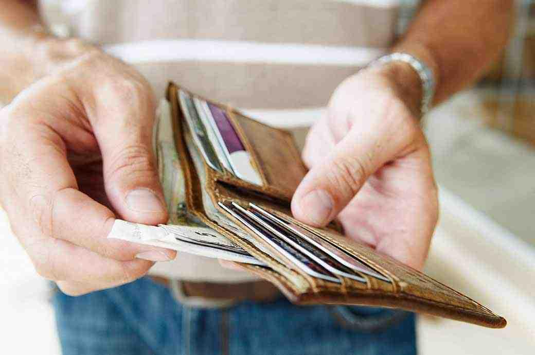 צילום תקריב של אדם מוציא שטרות מארנק