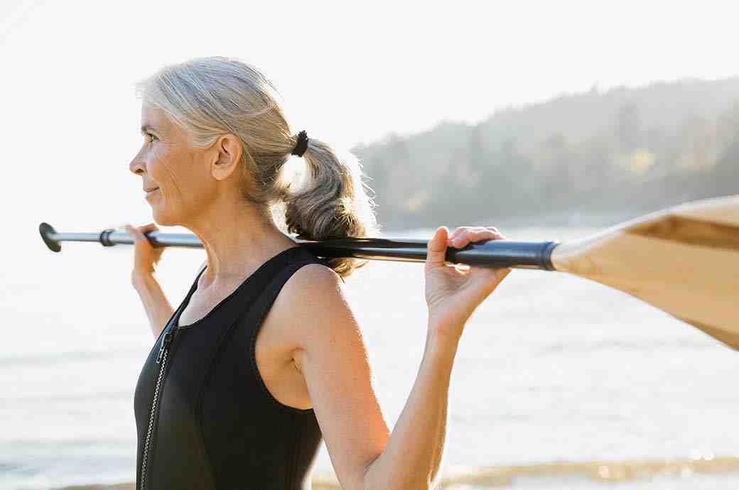 תמונה של אישה בוגרת בשטח פתוח עם משוט