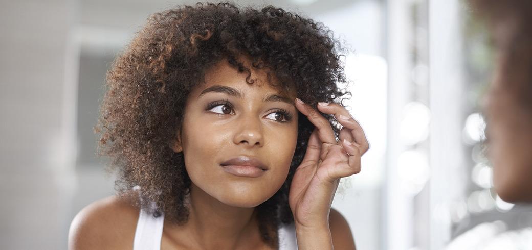 אישה צעירה מביטה בעיניה במראה